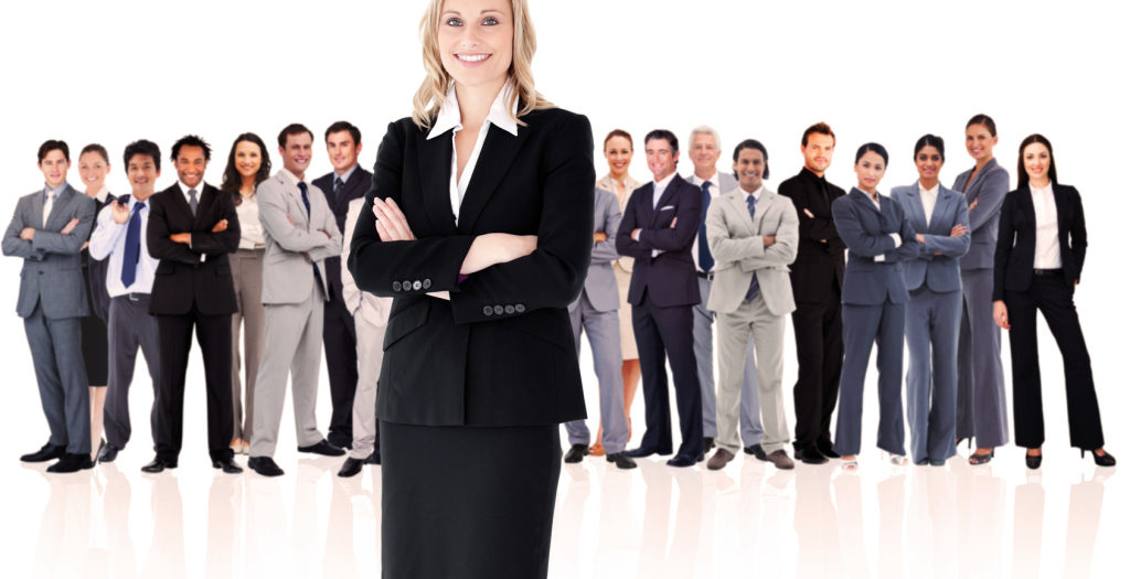 Businesswoman standing up with colleagues in background